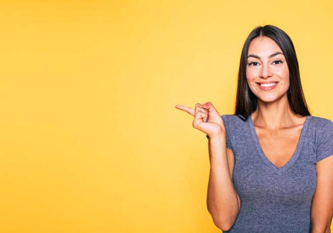 Photo of young excited beautiful happy brunette woman, girl pointing away and smile isolated on yellow background banner